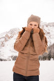 Woman hiding behind collar outdoors among snow-capped mountains Royalty Free Stock Photography