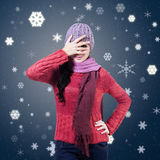 Woman Hiding Behind Hands. Woman wearing knitted scarf and hat hiding behind hands on winter background Royalty Free Stock Image