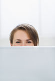 Woman hiding behind laptop Royalty Free Stock Photo