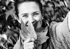Woman hiding behind leaf while making selfie in fron. Happy young woman hiding behind leaf while making selfie in front of autumn foliage Royalty Free Stock Photos