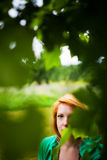 Woman hiding behind leaves stock photo