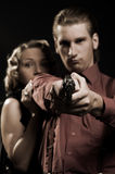 Woman hiding behind the man with gun Stock Image