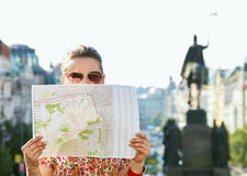 Woman hiding behind map while standing at Wenceslas Square. Catch the spirit of old Europe in Prague. Young woman in sunglasses hiding behind a map while Stock Photos