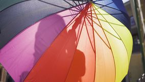 The woman hiding behind multicolored umbrella standing on the street. Unrecognizable girl enjoying sunny day in the old. The woman hiding behind a multicolored stock footage