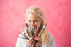 Woman hiding behind paint brushes Stock Photos