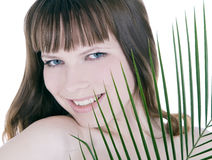 Woman hiding behind the palm leaf Royalty Free Stock Photo
