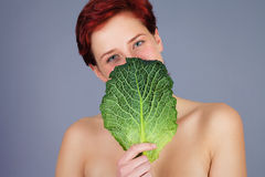 Woman hiding behind savoy cabbage leaf Royalty Free Stock Images