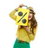 Woman hiding behind shopping bag symbolising beginning of sales Royalty Free Stock Image