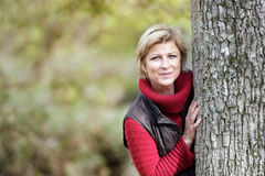 Woman hiding behind a tree. Timid woman hiding behind a tree Stock Images