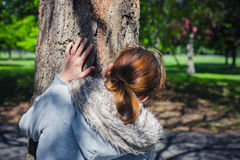 Woman hiding behind tree in park. A young woman is hiding behind a tree in the park Royalty Free Stock Photography
