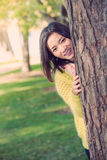 Woman hiding behind a tree. Portrait of shy young woman peaking from behind a tree and smiling Royalty Free Stock Photography