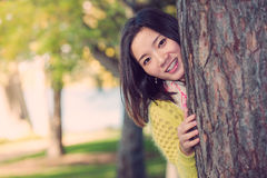 Woman hiding behind a tree. Portrait of shy young woman peaking from behind a tree and smiling Stock Photos
