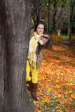 Woman hiding behind tree and showing thumb up. Happy woman peeking out from behind tree in park in autumn and showing thumb up Royalty Free Stock Photos