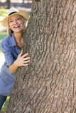 Woman hiding behind tree trunk Stock Photos