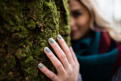 Woman hiding behind tree trunk Stock Image