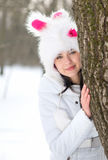 Woman hiding behind tree in winter Royalty Free Stock Photo