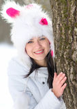 Woman hiding behind tree in winter. Season Stock Images