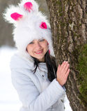 Woman hiding behind tree in winter. Season Royalty Free Stock Images