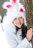 Woman hiding behind tree in winter Royalty Free Stock Photography