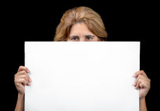 Woman hiding behind a white banner with space for text. (isolated on black Stock Photos