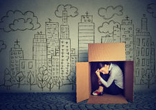 Woman hiding in the box on skyscraper city background. Young woman hiding in the box on skyscraper city background Royalty Free Stock Image