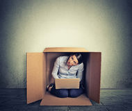 Woman hiding in the box working on computer Stock Images