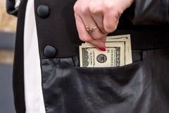 Woman hiding dollars into the jacket.  Royalty Free Stock Photo