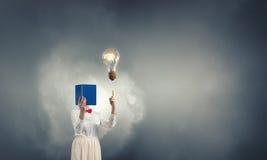 Woman hiding face behind book Stock Photography