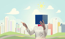 Woman hiding face behind book Stock Images