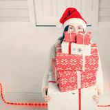 Woman hiding face behind Christmas gift boxes. Young woman hiding her face behind Christmas gift boxes while sitting on doorstep outdoors Stock Image