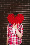 Woman hiding face from heart shape Stock Photography