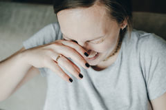 Woman hiding face laughing through hands. Royalty Free Stock Images