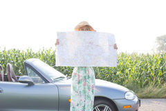 Woman hiding face with map by convertible against clear sky Stock Photography