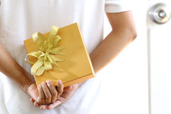 Woman hiding gold gift box Royalty Free Stock Images