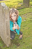 Woman hiding in graveyard. Desperate looking young woman kneeling down behind a gravestone in a  grassy graveyard Stock Photos