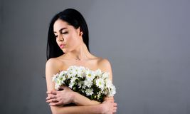Woman hiding her breasts, covers with bouquet. Picture of woman holds bunch of lovely chamomile flowers, grey background. Cancer of breast concept. Lady covers Stock Photography