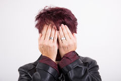 Woman hiding her face. Woman against White Background is hiding her face Stock Images