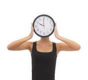 A woman hiding her face behind a clock Stock Photos