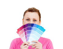 Woman hiding her face behind color sample. Standing against white background Stock Images