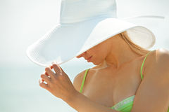 Woman hiding her face behind her white hat Royalty Free Stock Images