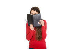 Woman hiding her face behind a notebook. Royalty Free Stock Image