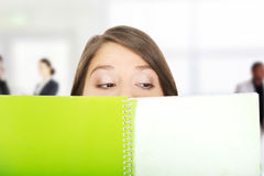 Woman hiding her face behind a notebook. Stock Image