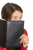 Woman hiding her face behind a notebook. Young woman hiding her face behind a notebook Stock Image