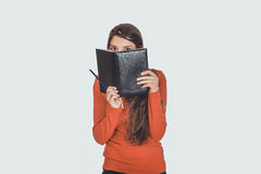 Woman hiding her face behind a notebook. Royalty Free Stock Images