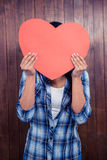 Woman hiding her face behind paper heart Stock Image