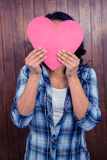 Woman hiding her face behind paper heart Royalty Free Stock Photos
