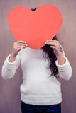 Woman hiding her face behind paper heart Stock Photography