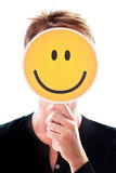 Woman hiding her face behind a smiley. Woman hiding her face behind an happy smiley Stock Photos