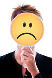 Woman hiding her face behind a smiley. Woman hiding her face behind an unhappy smiley Royalty Free Stock Image