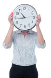 Woman hiding her face behind wall clock Stock Image